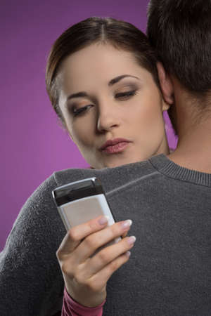 Infidelity  Attractive young woman typing a message on her mobile phone while hugging with her boyfriend photo