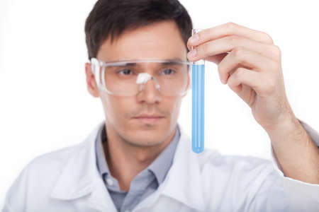 biochemist: Biochemist at work. Confident young man in protective eyewear holding laboratory glass with blue liquid while isolated on white