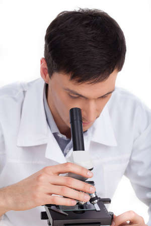 Scientist. Confident young man looking through microscope while isolated on white photo