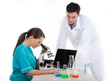 Chemical experiment. Two confident young people in lab coat making scientific experiment together while isolated on white photo