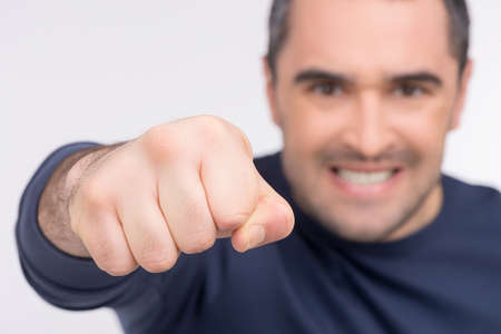 Close up of man twist. Angry male face on blur background