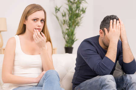 Adult couple having big trouble in relations. Woman sitting with sad expression and bruises on face photo