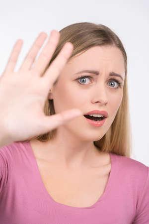 maltrato: Niña rubia diciendo no mirando a la cámara. Aislado en blanco