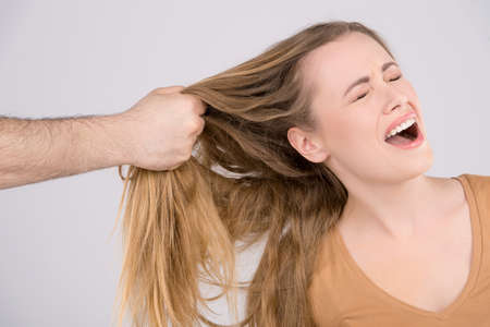 Man hitting a young woman. Close up of hand pulling female hair photo