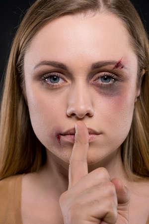 keep silent: Primo piano di panna montata femmina bionda. Tenendo il dito, mostrando di tacere Archivio Fotografico