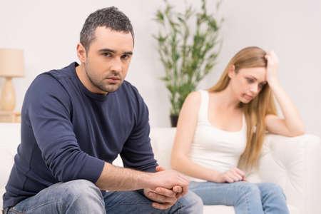 pareja discutiendo: Hombre deprimido triste en primer plano. Asustada mujer triste en el fondo