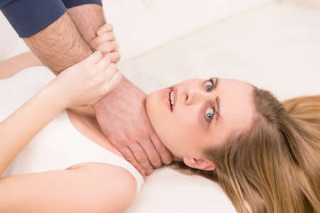 Close up of scared woman being strangled. Fighting with her boyfriend in a bed Stock Photo - 23473945
