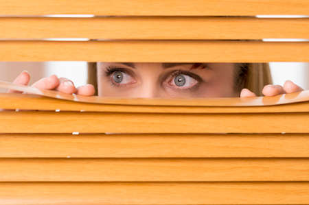 Close up of female eyes looking outside from blinds. Bruise on woman face photo