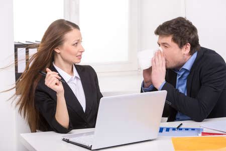 Flu. Man sneezing while sitting near his coworker photo