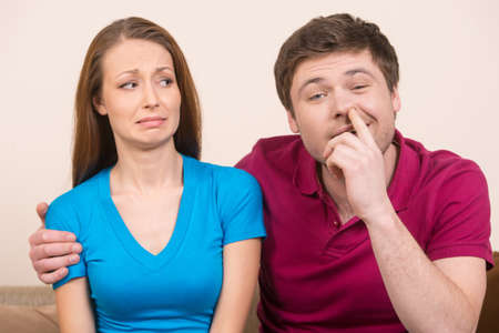 nose picking: Man picking nose. Young man picking nose while sitting close to his girlfriend