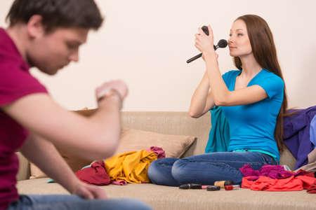 hurry up: Per favore sbrigati! Donna facendo il make-up, mentre il suo ragazzo guardando i suoi orologi