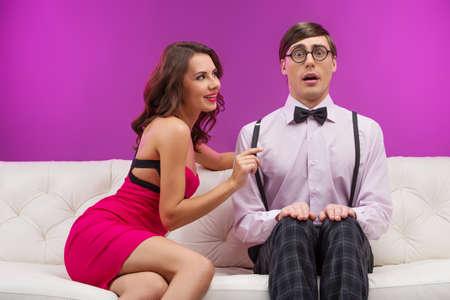 femme sexe: Timide nerd. Choqué homme ballot assis près de la belle jeune femme et regardant la caméra Banque d'images