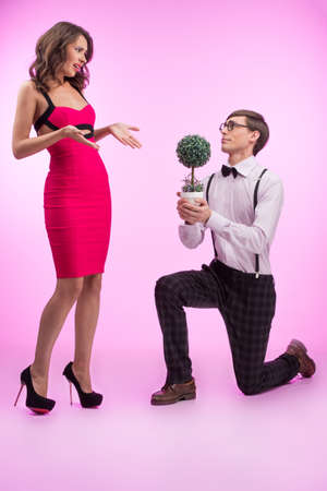 Nerd and beauty. Young nerd man standing at his knee and holding flower while beautiful young woman in red dress looking at him photo
