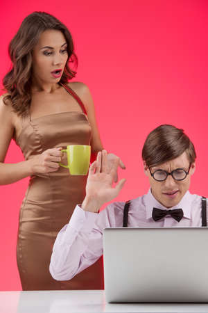Nerd with girlfriend. Confident nerd man working at the computer while beautiful young woman standing near him and holding cup photo