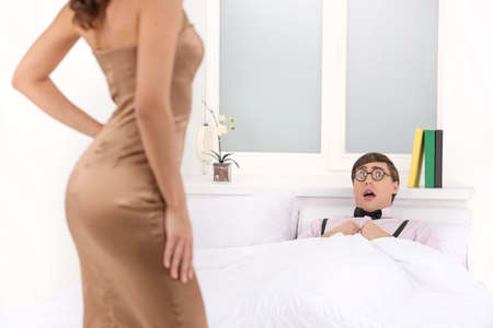 Nerd and beauty. Scared nerd man lying on the bed and looking at beautiful woman in dress photo