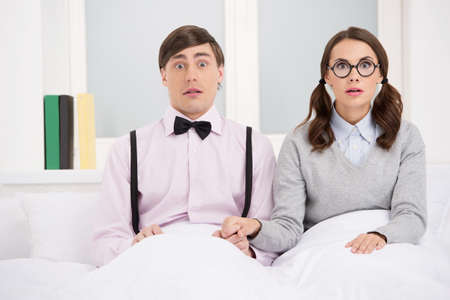 Nerd couple. Surprised nerd couple sitting on the bed and looking at camera photo