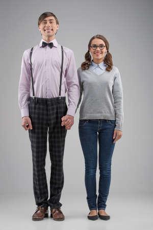 Nerd couple. Full length of happy nerd couple standing isolated on grey photo