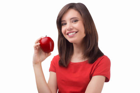 Beauty with apple. Beautiful young women holding red apple and smiling while standing isolated on white photo