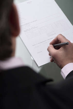 Signing an agreement. Top view of businessman signing a contract photo