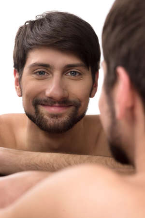 Man looking at mirror. Young man looking at himself at the mirror and smiling photo