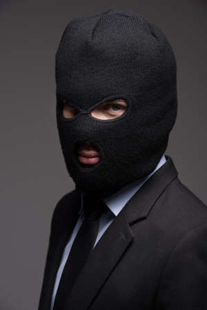 white collar crime: White collar crime. Portrait of businessman in black balaclava looking at camera while isolated on grey
