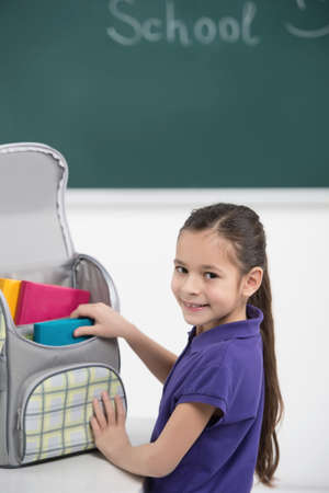 packing supplies: Packing her book bag. Cheerful little schoolgirl packing her book bag and smiling at camera Stock Photo