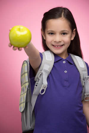 Schoolgirl with apple. Cheerful little schoolgirl holding an apple and smiling at camera while standing isolated on coloured background photo