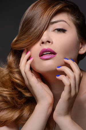 Multi colored nails. Portrait of beautiful women touching face with her hands while isolated on black photo