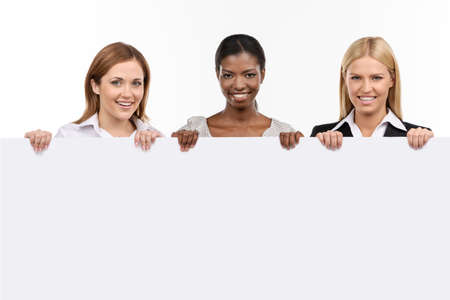 three people only: businesswomans holding white board looking at camera