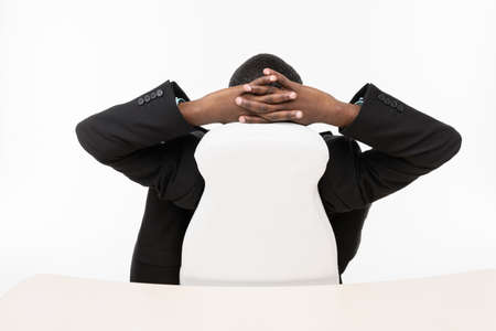 Businessman sitting with hands behind head photo