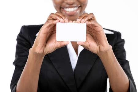 traje sastre: Empresaria del afroamericano que sostiene la tarjeta de visita en el fondo blanco. Cierre
