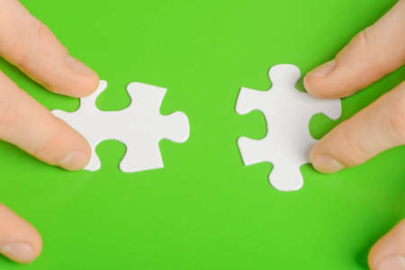 Hands and puzzle isolated on green background photo