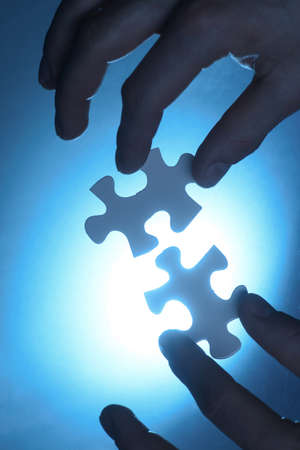 two pieces: hands trying to fit two puzzle pieces together. Stock Photo