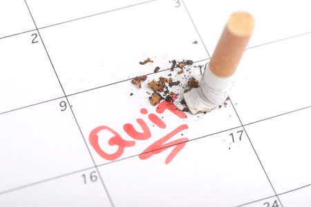 quit smoking: Cigarette stubbed out on a day on the calendar. Concept of choosing a day to quit smoking Stock Photo