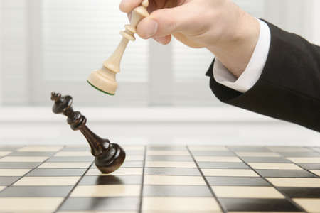 chess board: High key image of a Chess board. Checkmate by the black Pawn. Stock Photo