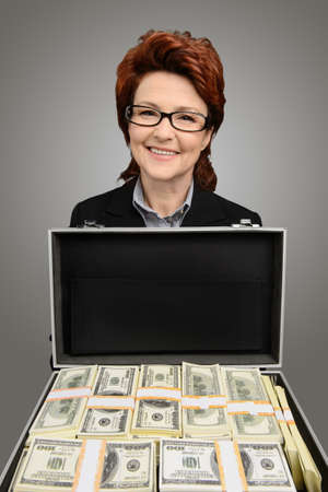 Businesswoman holds up a briefcase full of money. Isolated on gray photo