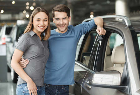 We have made the right choise. Handsome young men standing near the car at the dealership hugging his girlfriend and holding a key Stock Photo