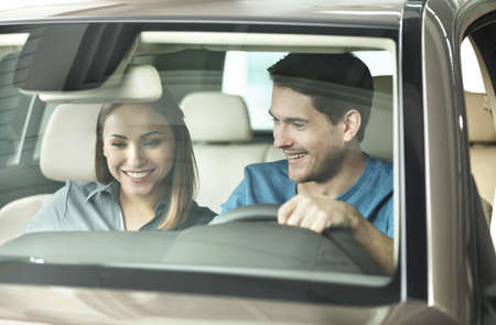 Look at this console! Beautiful young couple sitting at the front seat of the car checking out the side panel photo
