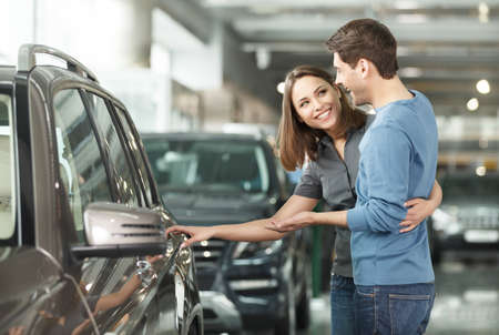 It is the one car I want! Beautiful young couple standing at the dealership choosing the car to buy photo