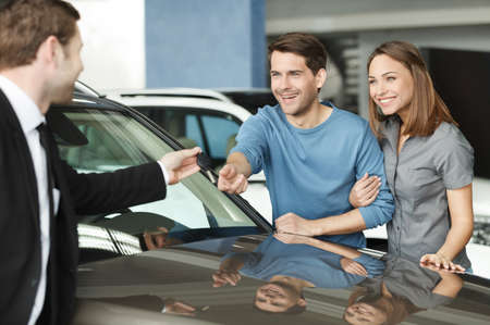 They have made a right vehical choise. Young car salesman giving a key from the new car to the beautiful young owners photo