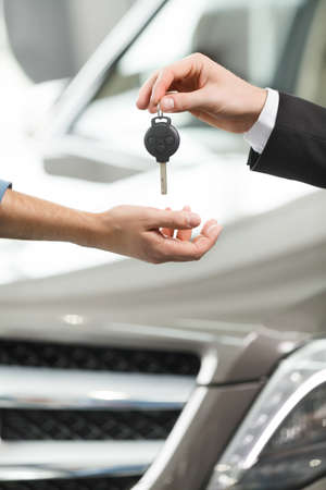 outstretching: Drive carefully! Close-up shoot of the car salesman hand giving a key to the owner