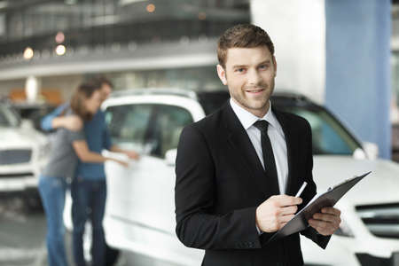 Let me assist you in your vehicle search. Handsome young classic car salesman standing at the dealership with the customers on the background