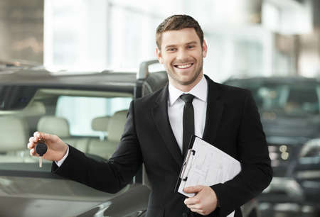 Great choise! Handsome young classic car salesman standing at the dealership holding a key photo