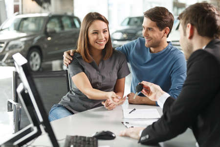 Now her dream comes true. Car salesman giving the key of the new car to the young attractive owners photo