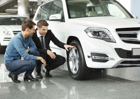 Look at these tires! Young car salesman showing the advantages of the car to the customer photo
