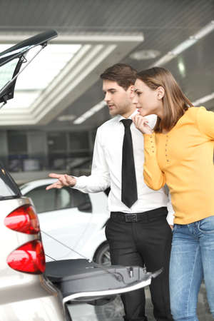 roomy: It?s so roomy inside. Handsome young car salesman showing the car trunk to the customer