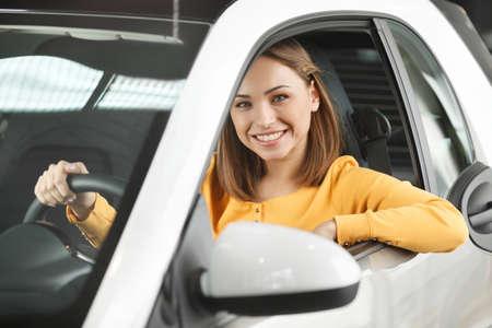 dream car: Ella ha comprado su coche de ensueño! Atractiva joven sentado en el asiento delantero del coche mirando a la cámara Foto de archivo