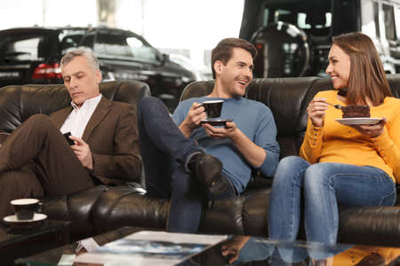 car dealership: They need some break to make a right choise. Three car dealership customers having a break before making final decision about car they want