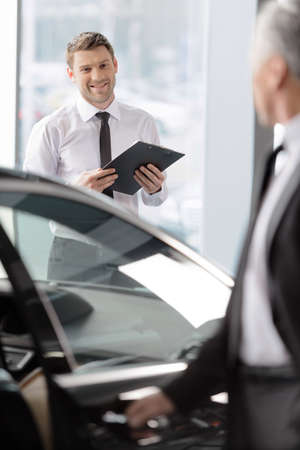 knew: I knew you� like this car. Handsome young classic car salesman standing in the dealership and helping a client to make a decision Stock Photo