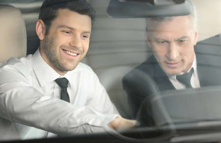 car dealership: Let me show you all the features  Handsome young classic car salesman sitting at the front seat of the car showing the features to a client Stock Photo